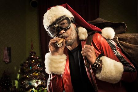 hombre fumando puro: Bad Santa con gafas y cigarro que llevan un saco con regalos.