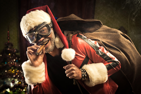 Bad Santa with goggles and cigar carrying a sack with gifts.