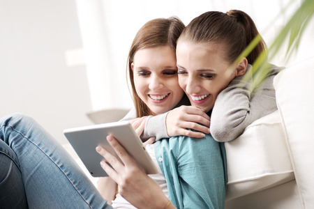 homosexual couple: Happy lesbian couple spending time together with tablet on sofa at home. Stock Photo