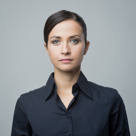 frontal view: Serious confident woman in blue shirt staring at camera.