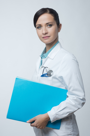 cardiovascular: Smiling young female doctor holding medical records file.
