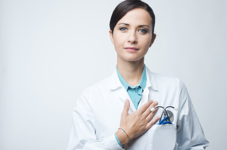 Attractive female cardiologist with stethoscope and lab coat, touching her chest.