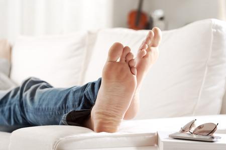 pies descalzos: Joven se relaja en el sofá en la sala de estar, con los pies cerca. Foto de archivo