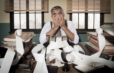 desk clerk: Desperate accountant head in hands surrounded by bills on paper tape, 1950s style office.