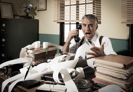 Angry vintage businessman shouting out loud at phone surrounded by adding machine tape. photo