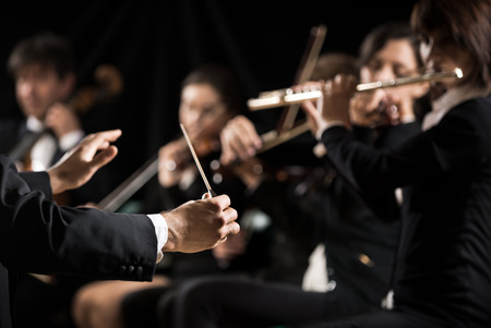 orquesta: Conductor dirigir orquesta sinfónica con intérpretes en el fondo. Foto de archivo