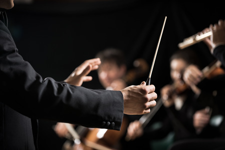 strings: Conductor directing symphony orchestra with performers on background, hands close-up.
