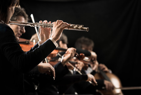 symphony: Female flutist close-up with orchestra performing on background. Stock Photo