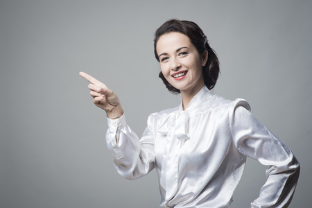 Attractive vintage woman in elegant shirt pointing up and smiling photo