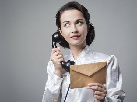 retro telephone: Vintage secretary on the phone holding a closed envelope Stock Photo