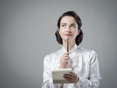 mujer pensativa: Toma secretario notas atractivas de la vendimia con el bloc de notas y un bol�grafo