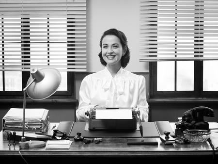 陽気なビンテージの秘書のオフィスの机で働いて、カメラに笑顔