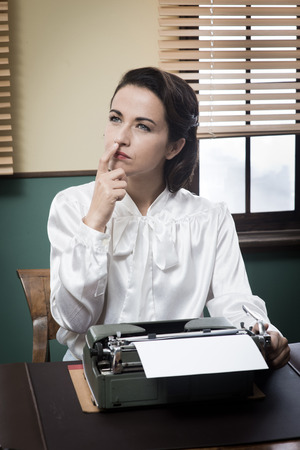 Pensive vintage woman with hand on chin, typing on typewriter and looking for inspiration Reklamní fotografie