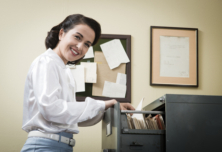 woman searching: Smiling vintage secretary searching files in the filing cabinet drawers