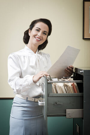 file clerks: Smiling vintage secretary searching files in the filing cabinet drawers
