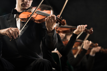 Violinists performing on stage on dark background. photo