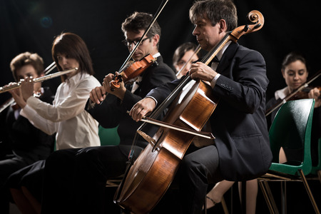 concert flute: Symphony orchestra on stage, violins, cello and flute performing. Stock Photo