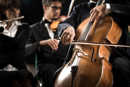 musical instruments: Symphony orchestra performing with cello player hand close-up.