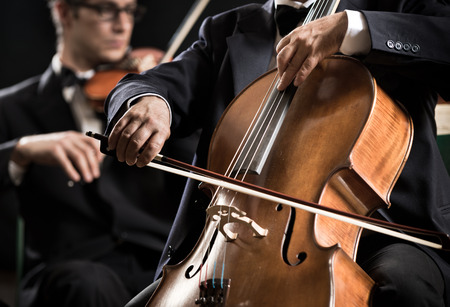 violin: Cello professional player with symphony orchestra performing in concert on background.