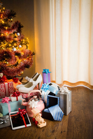 christmas train: Christmas gifts for all family under decorated tree with lights and colorful baubles.