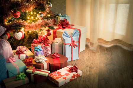 Elegant christmas tree with decorations and gifts on elegant hardwood floor. photo