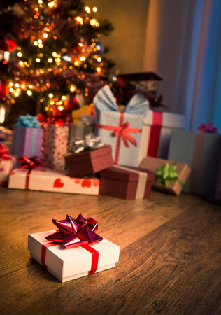 warm home: Special christmas gift with decorated tree on background. Stock Photo