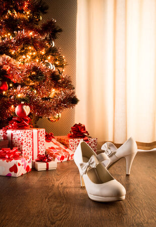 White female elegant shoes with christmas tree and presents on background. photo
