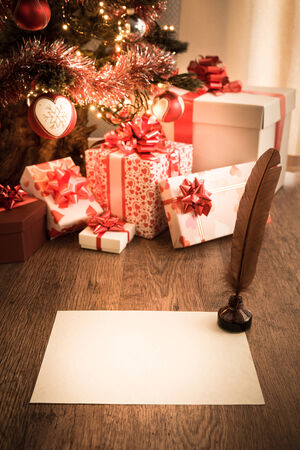 wishlist: Old letter with feather pen on wooden table with christmas tree and gift boxes. Stock Photo
