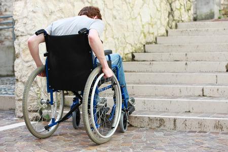 Een jonge man in een rolstoel die niet kunnen krijgen de trap Stockfoto
