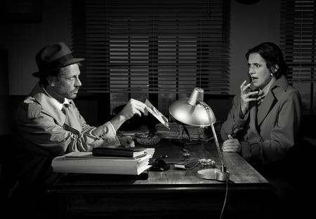 investigacion: Detective hermoso en el escritorio de oficina muestra una imagen para una mujer joven, escena del cine negro.