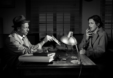 office force: Handsome detective at office desk showing a picture to a young woman, film noir scene.
