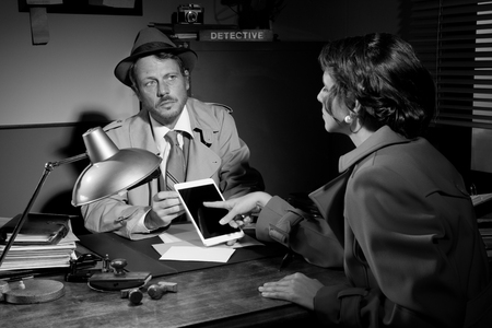 Woman touching detective's tablet sitting at his office desk. Stock Photo