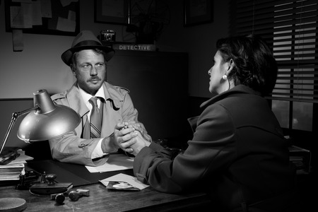 Handsome supportive detective at office desk holding a young womans hands and comforting her, film noir. Stock Photo