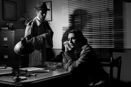 office force: Detective interviewing a young sad woman in his office, film noir scene.