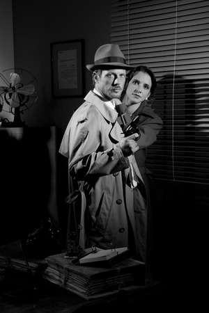 office force: Passionate 1950s couple embracing and looking scared at camera.