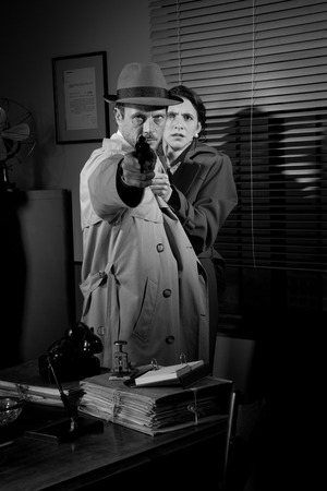 violence in the workplace: Brave detective pointing a gun and young scared woman hiding behind him, 1950s film noir style. Stock Photo