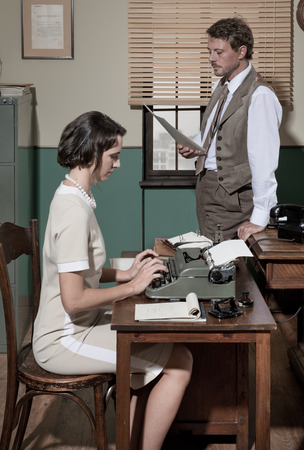 Director with paperwork and young secretary typing on typewriter in an elegant vintage office.