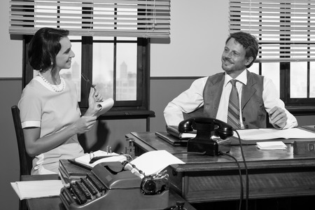 white collar worker: Director and secretary working together at desk, 1950s style office.
