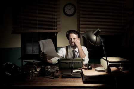 typewriter: 1950s reporter working late at night and proofreading his work.