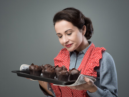baking tray: Smiling vintage woman holding a baking tray with chocolate home made muffins