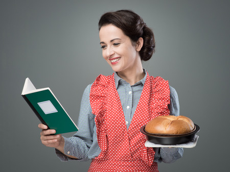 retro housewife: Smiling retro housewife holding a cookbook and a baking tin with a homemade cake Stock Photo