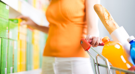 spending full: Young woman taking products from shelf at supermarket and holding a shopping cart.
