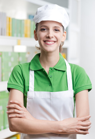 sales clerk: Young female sales clerk with crossed arms smiling at camera with supermarket shelf on background.
