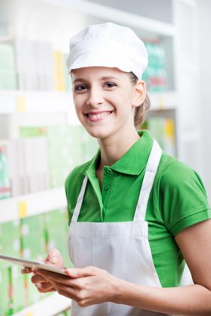sales clerk: Young female sales clerk posing with digital tablet at supermarket. Stock Photo