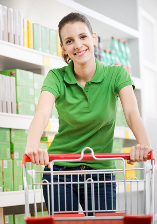 Smiling young woman at supermarket pushing a shopping cart with shelves on background. photo