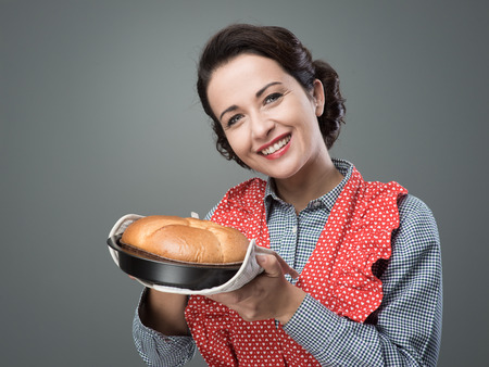Smiling vintage woman holding an homemade cake in a baking tin photo