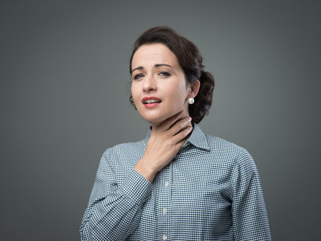 Vintage woman with sore throat touching her neck