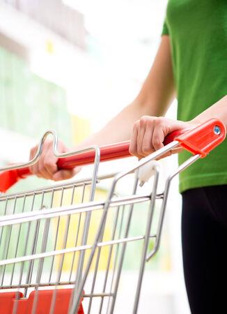 Mujer en la camiseta verde empujando un carrito de la compra en la tienda con estantes en el fondo.