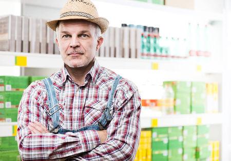 chapeau de paille: Confiant agriculteur au supermarché avec des étagères de magasin sur fond. Banque d'images