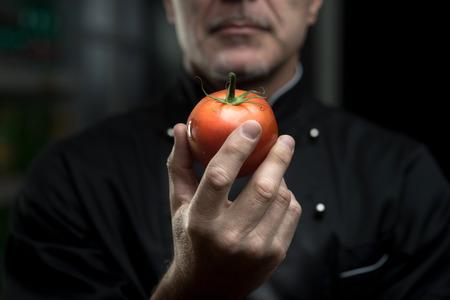 food preparation: Confident elegant chef holding a delicious tomato on dark background.